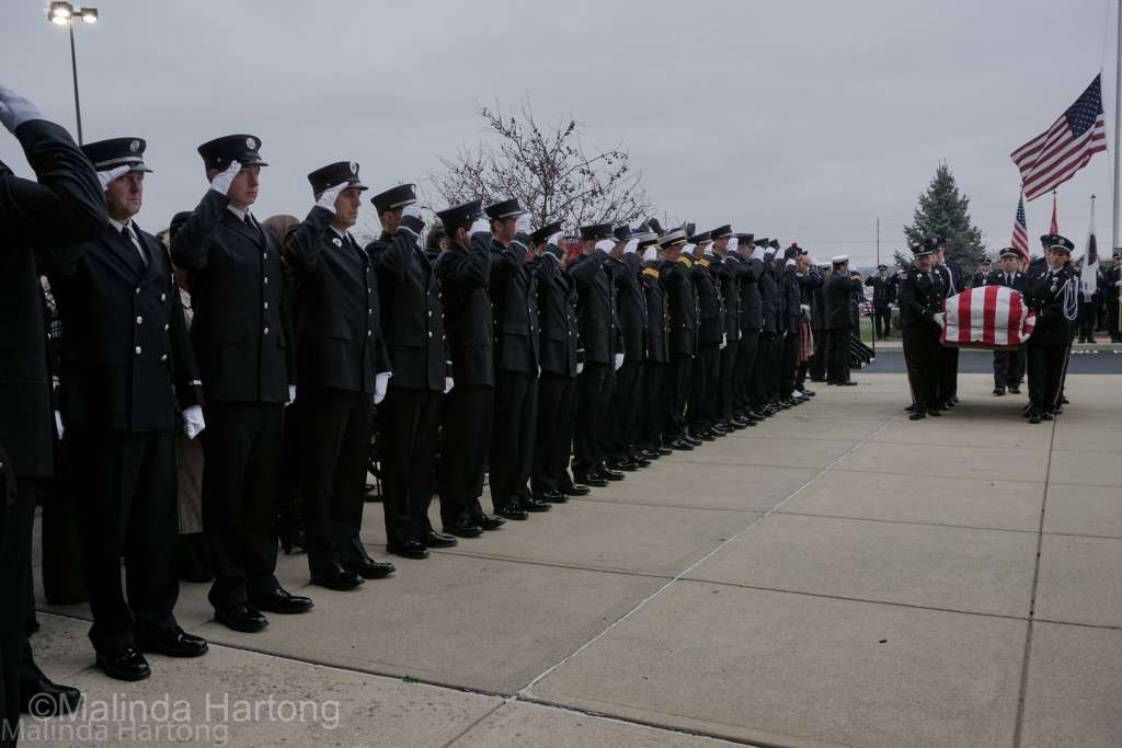 Hamilton firefighters salute as their fellow firefighters carry Firefighter Patrick Wolterman in to the services at Princeton Pike Church of God ©Malinda Hartong