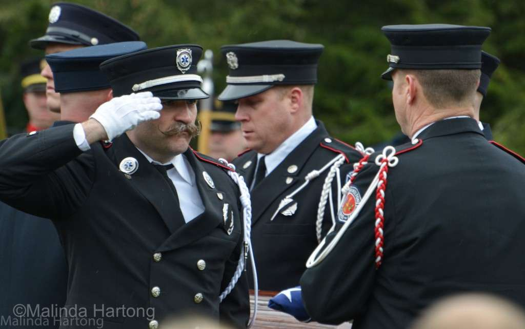 Having folded the flag covering Patrick Wolterman's casket, it's passed to Lt Nathaniel Robertson to give to Chief Dawson to present to Mrs Bre Wolterman, just wed to Patrick in May of this year and now a widow. ©Malinda Hartong