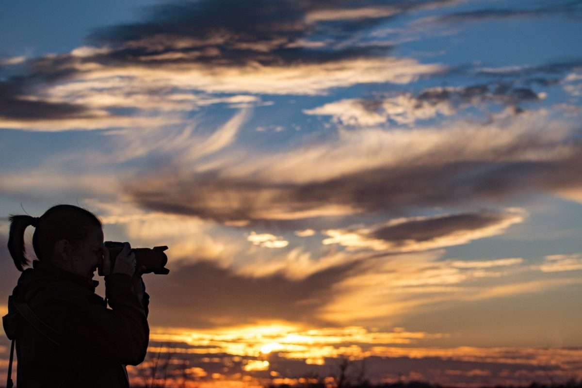 photo of a girl with camera at sunset