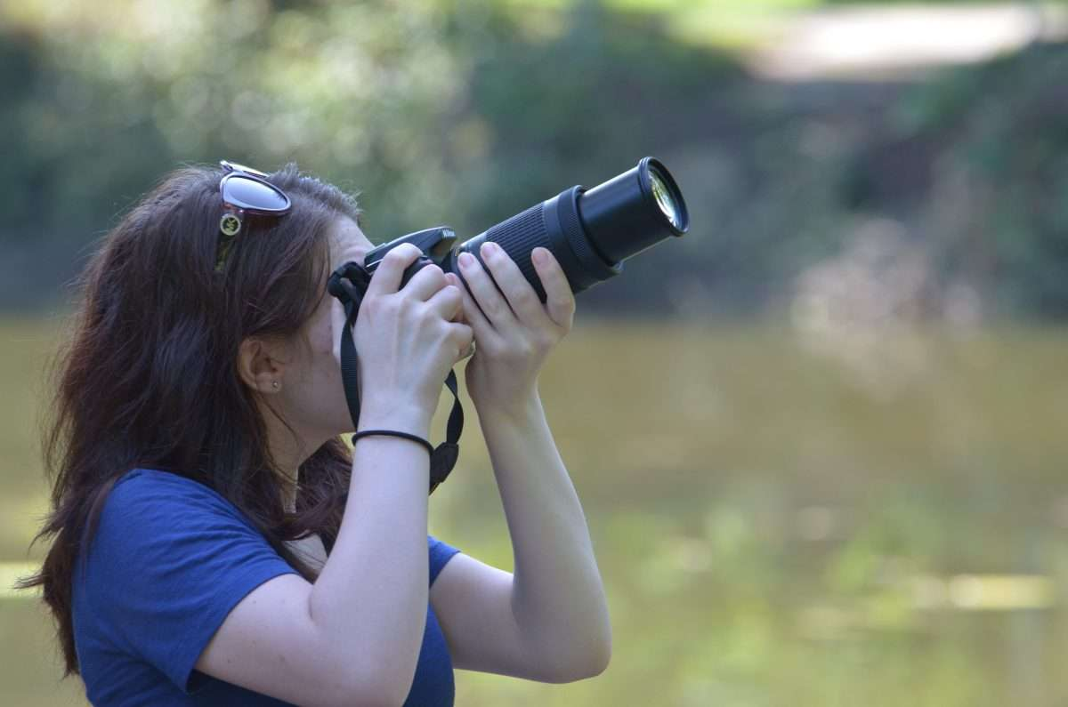 a teen uses her telephoto lens to capture images during summer camp