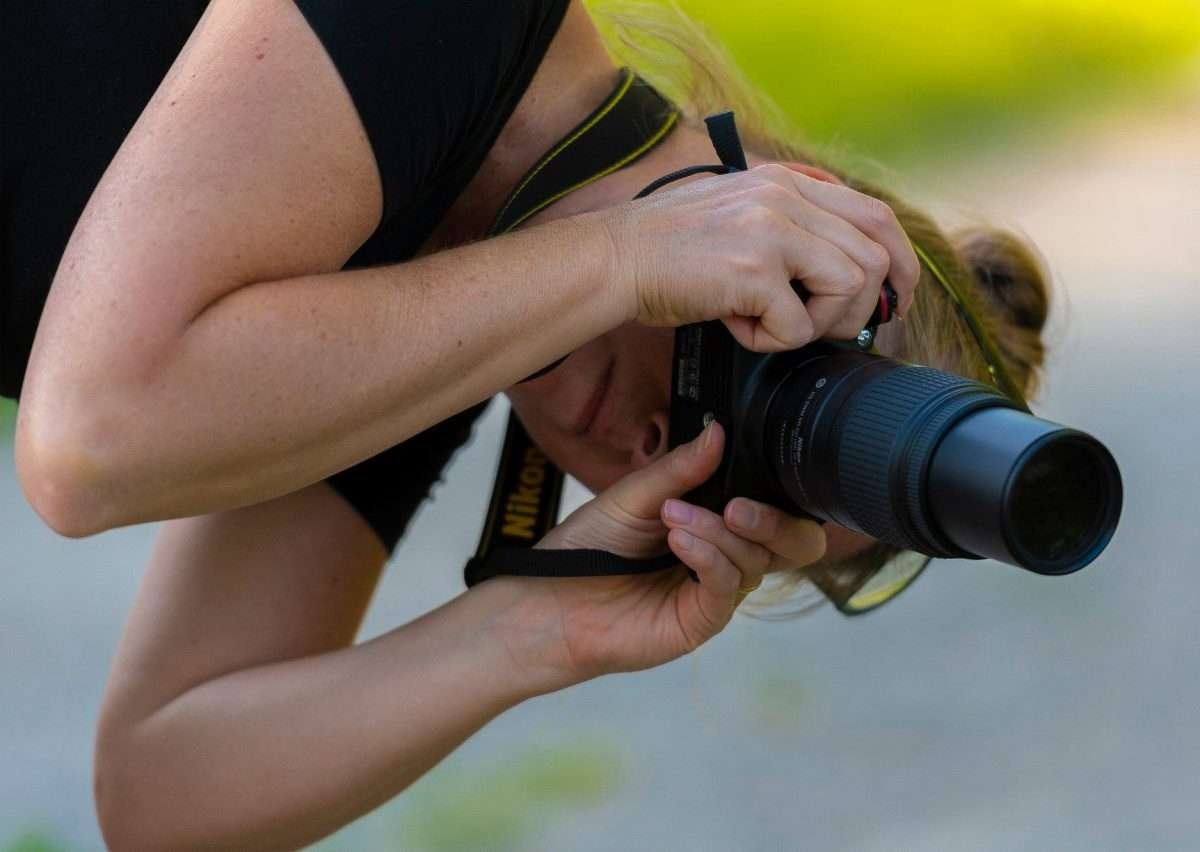 a woman leans over to capture a better background in her photo