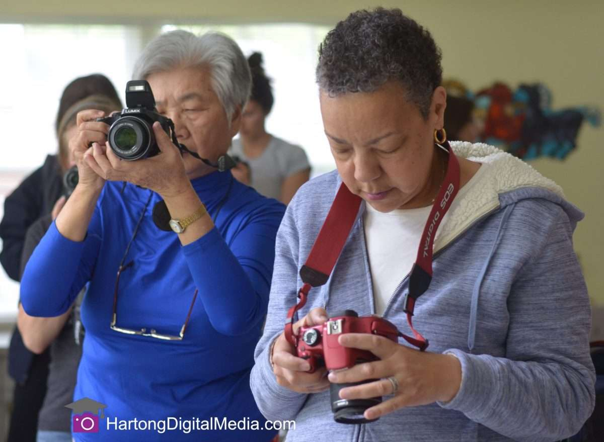 an asian american and an african american lady learn to use their cameras