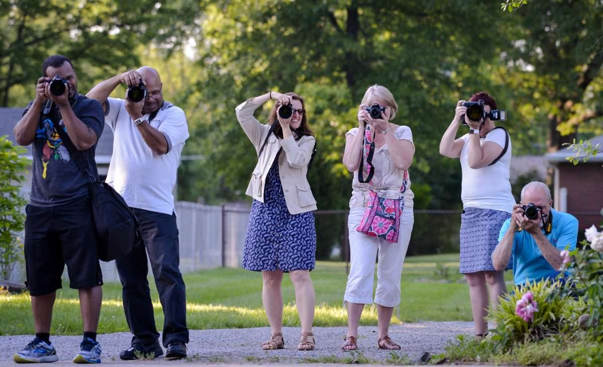 a group of people take pictures during a hands on camera class